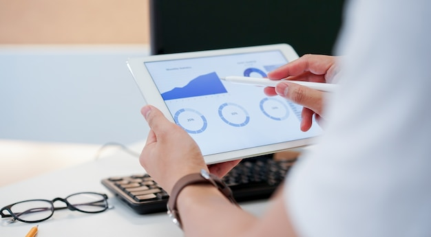 Uomo d'affari facendo uso della penna per pianificare la strategia finanziaria sul tablet con il cruscotto