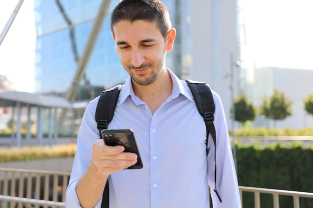 Uomo d'affari utilizzando app per smartphone sms messaggio sms in strada della città