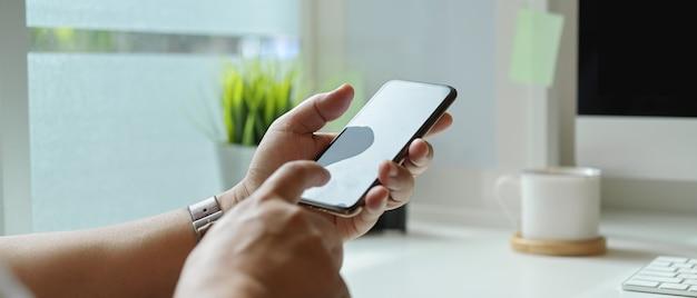 Uomo d'affari facendo uso dello smartphone mentre sedendosi alla scrivania moderna accanto alla finestra