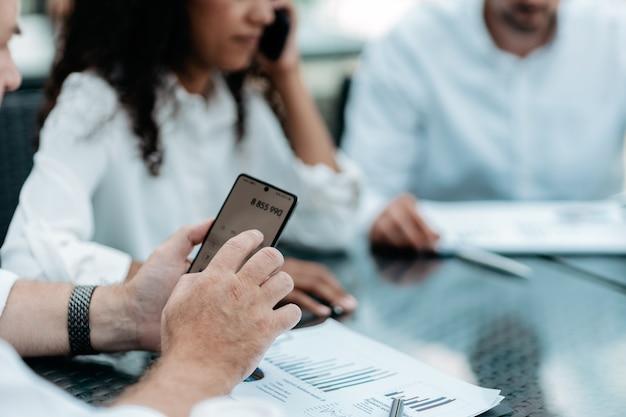 Uomo d'affari che utilizza uno smartphone mentre si lavora con documenti finanziari
