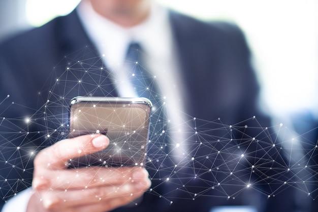Uomo d'affari utilizza lo smartphone con la connessione alla rete informatica globale