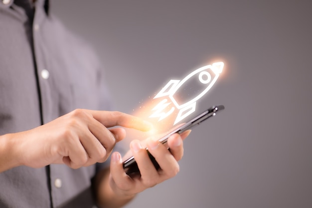 Uomo d'affari che utilizza smartphone con icona a razzo, concetto di successo aziendale veloce.
