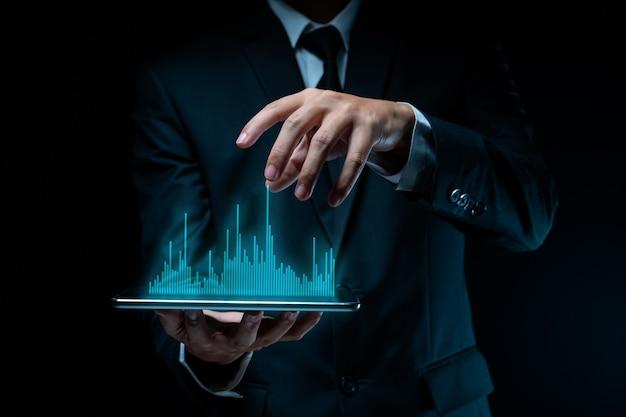Uomo d'affari utilizzando tablet pianificazione marketing digitale con effetto ologramma grafico