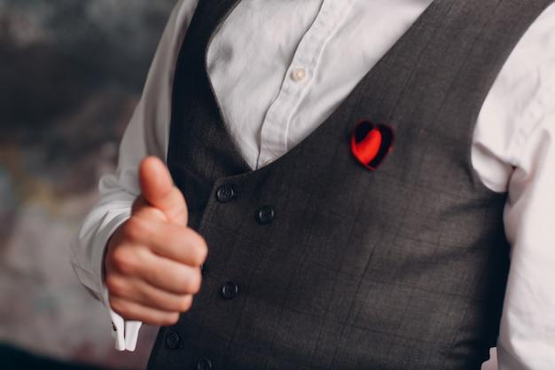 Gilet uomo d'affari con spilla a cuore e pollice in su. concetto di business e successo.