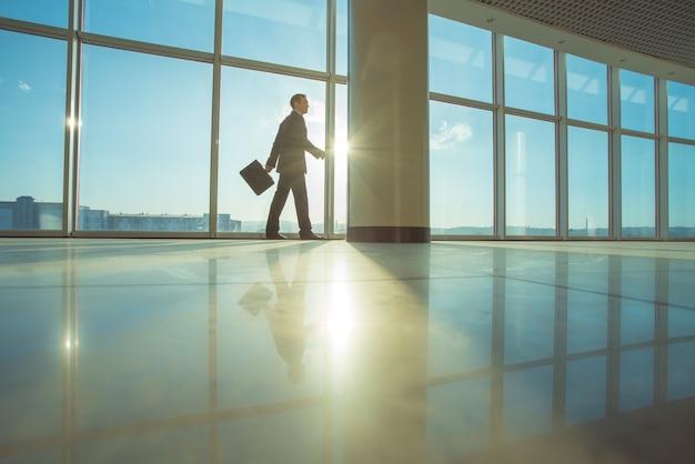 L'uomo d'affari cammina con una valigia nell'atrio dell'ufficio