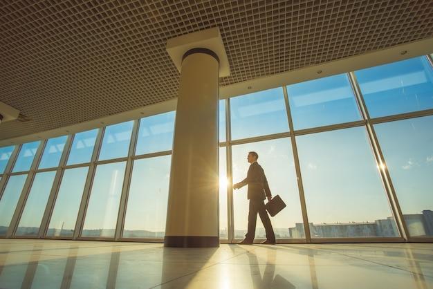 L'uomo d'affari cammina con una valigia nell'atrio dell'ufficio Foto Premium