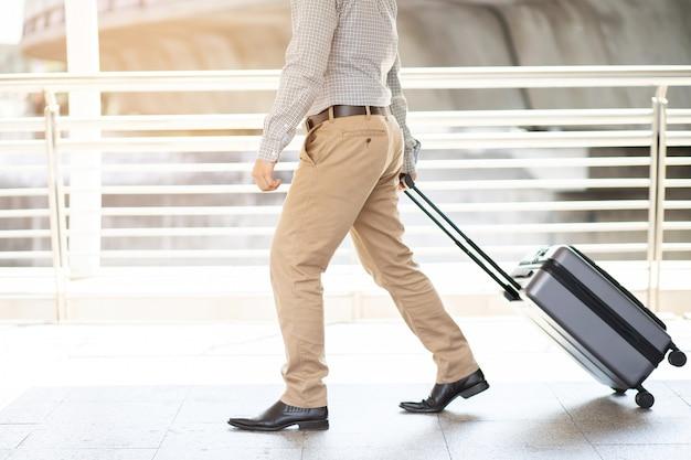 Uomo d'affari che cammina fuori dall'edificio dei trasporti pubblici con i bagagli nelle ore di punta. viaggiatore d'affari tirando la valigia nel moderno terminal dell'aeroporto. bagaglio viaggio d'affari.