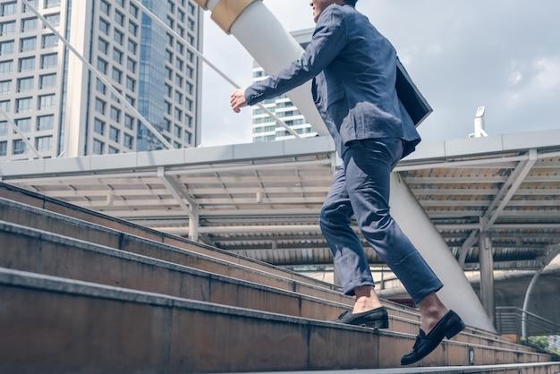 Uomo d'affari che cammina alla scala in città