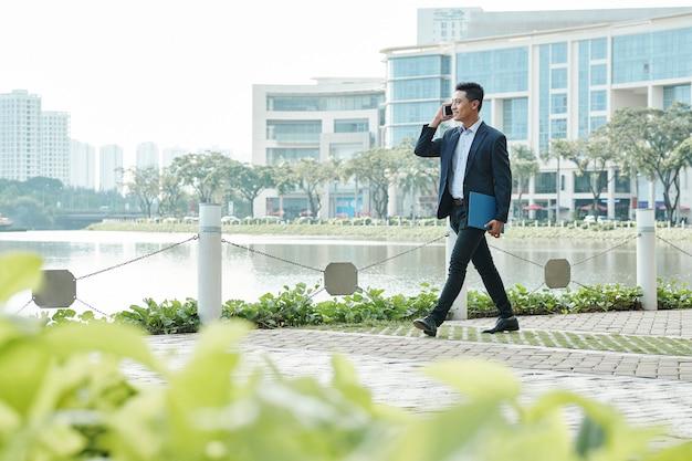 Uomo d'affari camminando e parlando al telefono