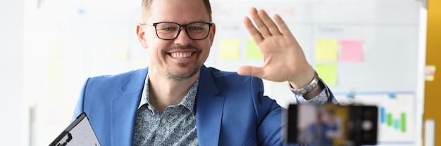 Uomo d'affari che agita la mano al concetto di conferenze di affari online della fotocamera del telefono cellulare