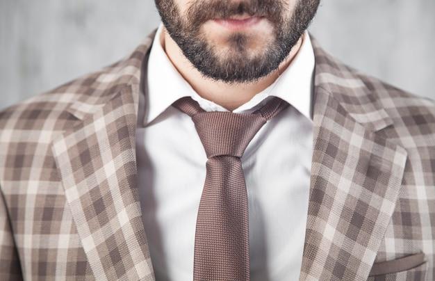 Uomo d'affari che indossa giacca e cravatta marrone.