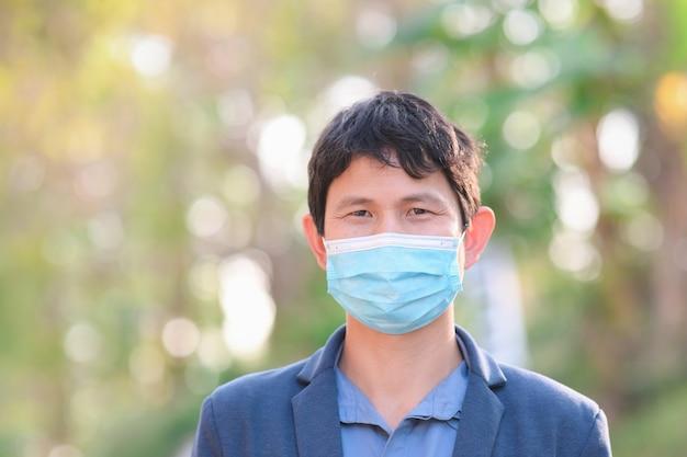 L'uomo d'affari che indossa una maschera di stoffa nell'area pubblica si protegge dal rischio di malattie, le persone prevengono l'infezione dal coronavirus covid-19