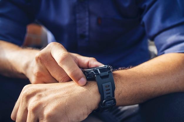 Uomo d'affari che indossa un orologio digitale intelligente in mano toccando lo schermo per aprire la notifica legge il messaggio e il tracker di attività al polso