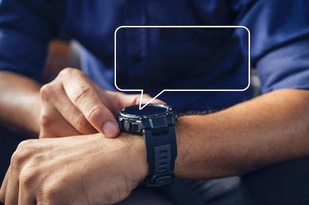 Uomo d'affari che indossa un orologio digitale intelligente in mano toccando lo schermo per aprire il messaggio di lettura della notifica