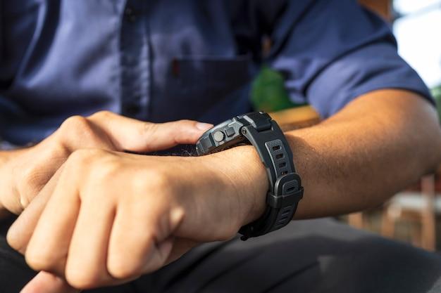 Uomo d'affari che indossa un orologio digitale intelligente in mano toccando lo schermo per aprire la notifica