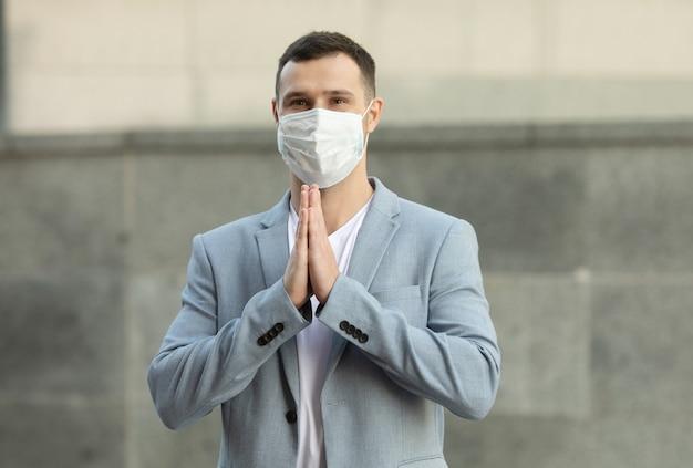 Uomo d'affari che indossa la maschera per il viso e saluto con namaste per prevenire la diffusione del virus