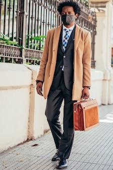 Uomo d'affari che indossa la maschera per il viso e in possesso di una valigetta mentre si cammina per lavorare all'aperto. nuovo stile di vita normale