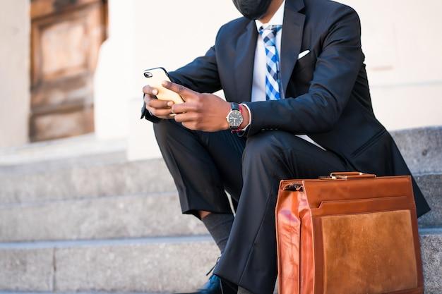 Uomo d'affari che indossa la maschera per il viso e utilizza il suo telefono cellulare mentre è seduto sulle scale all'aperto. nuovo stile di vita normale. concetto di affari.