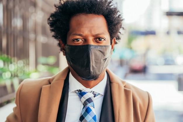 Uomo d'affari che indossa la maschera per il viso mentre si sta in piedi all'aperto sulla strada