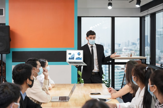 Uomo d'affari che indossa la maschera per il viso con la presentazione del business plan sul computer portatile