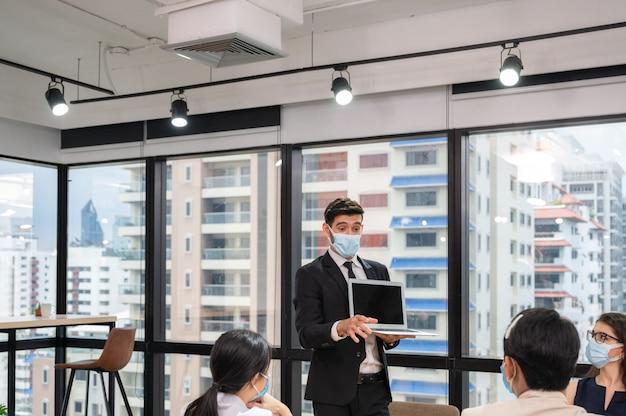Uomo d'affari che indossa la maschera per il viso con la presentazione del business plan sul laptop
