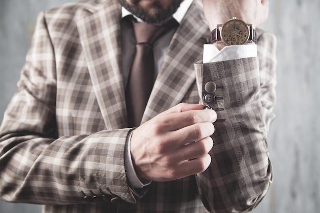 Uomo d'affari che indossa camicia e giacca in piedi in ufficio.