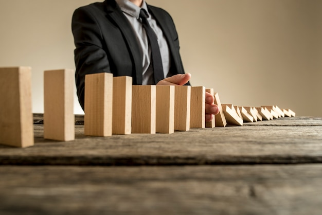 Un uomo d'affari che indossa un abito in piedi accanto a una serie di lastre di legno verticali mentre cadono uno dopo l'altro. concetto di effetto domino in cui un fallimento aziendale causa ulteriori crolli.