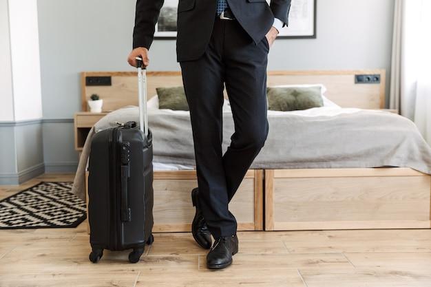 Uomo d'affari che indossa un abito in piedi nella camera d'albergo, portando la valigia, appena arrivato