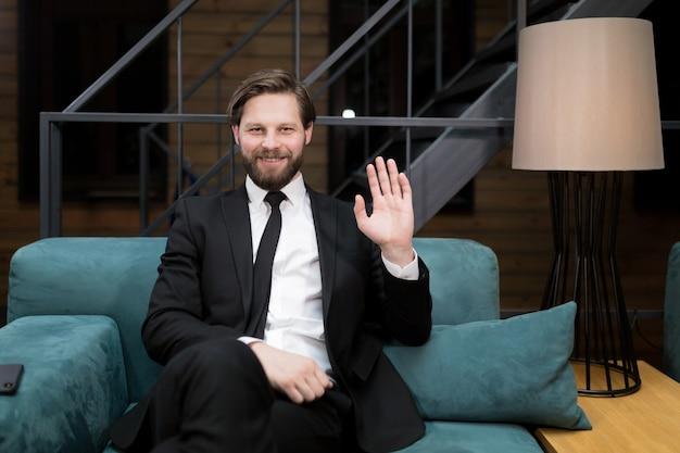 Uomo d'affari che indossa giacca e cravatta sorride alla telecamera mentre parla durante una conferenza d'affari online spiegando i dettagli del contratto al partner straniero tramite l'app di connessione