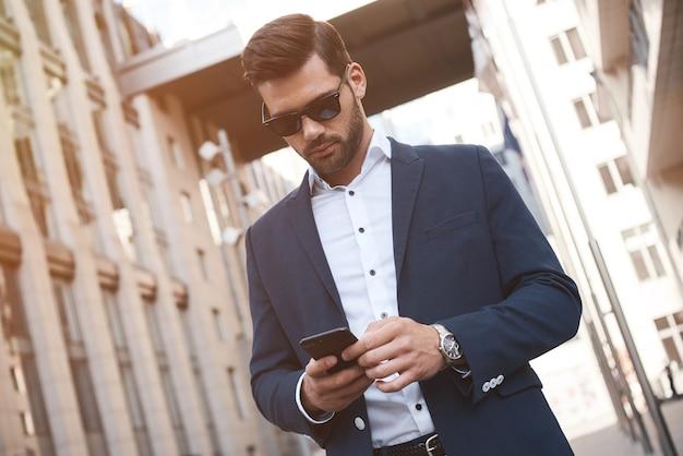 Uomo d'affari che indossa una tuta e utilizza uno smartphone moderno vicino all'ufficio al mattino presto con successo