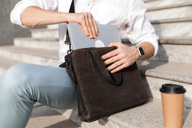 Uomo d'affari che indossa occhiali da sole, mettendo il computer portatile nella sua borsa, mentre era seduto sulle scale sulla strada della città