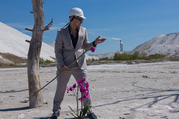Uomo d'affari in un casco protettivo bianco sullo sfondo della zona industriale protegge un fiore di orchidea. concetto ecologico di protezione ambientale.