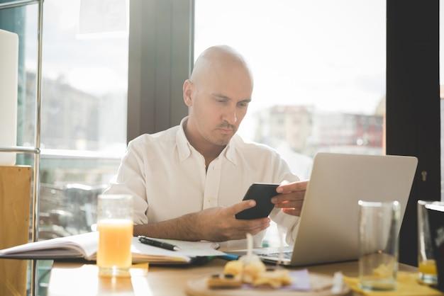 Uomo d'affari in camicia bianca che lavora al tavolo dell'ufficio