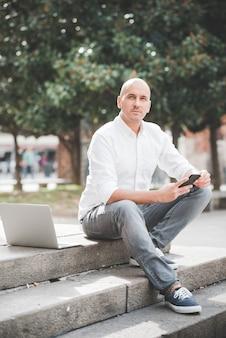 Uomo d'affari in camicia bianca che lavora con il computer portatile che si siede sulla scala