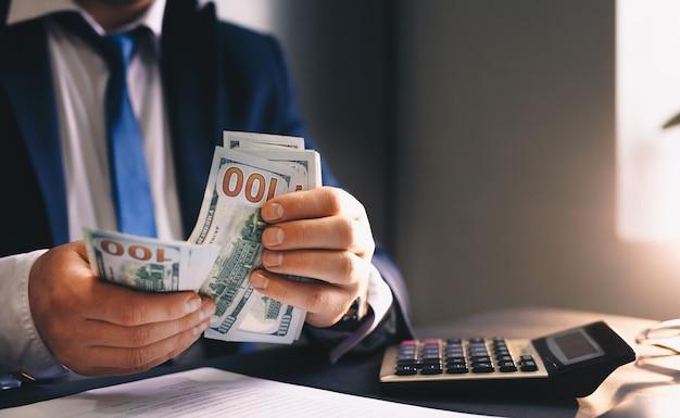 Uomo d'affari che conta e calcola i suoi guadagni