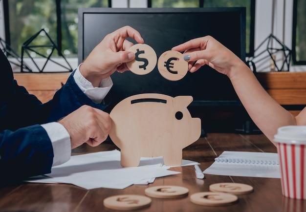 L'uomo d'affari con un impiegato di banca tiene le monete sotto un maiale di legno. salvadanaio. raccogliere denaro con la banca dei guadagni.