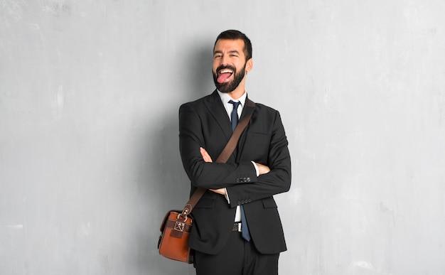Uomo d'affari con la barba che mostra la lingua alla macchina fotografica che ha sguardo divertente