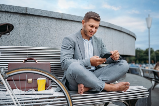 Uomo d'affari con la bici che riposa sul banco all'edificio per uffici nel centro