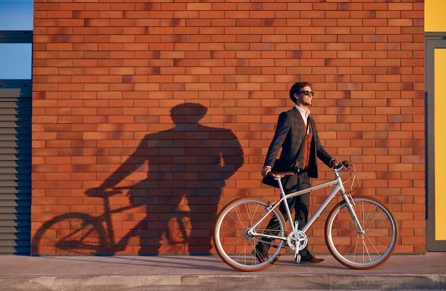 Uomo d'affari con la bici che cammina vicino al muro di mattoni