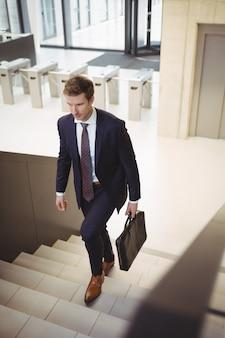 Uomo d'affari con valigetta salire le scale