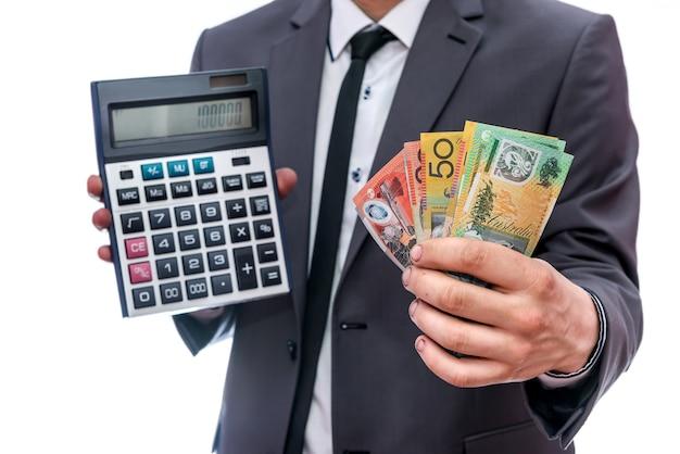 Uomo d'affari con calcolatrice e dollari australiani isolati