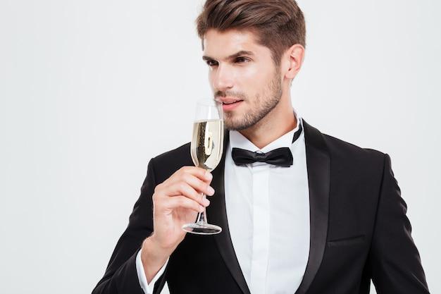 Uomo d'affari con champagne che guarda lontano. isolato