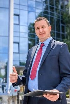 Uomo d'affari con appunti in piedi contro il nuovo edificio