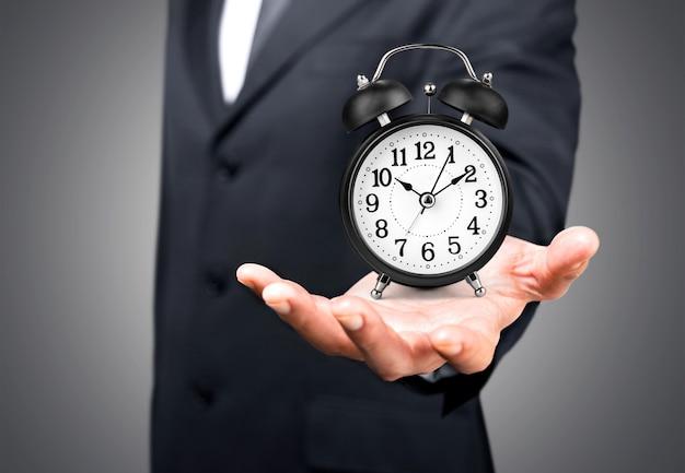 Uomo d'affari con il concetto di orologio in tempo sullo sfondo