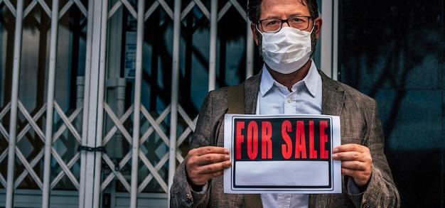 Uomo d'affari con cartello chiuso fuori dal suo negozio per crisi economica del coronavirus