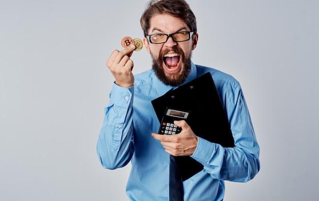Uomo d'affari con una moneta nelle sue mani, criptovaluta bitcoin e una calcolatrice