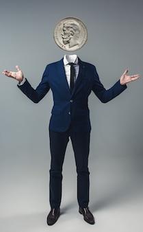 Uomo d'affari con una moneta al posto della testa su sfondo grigio studio