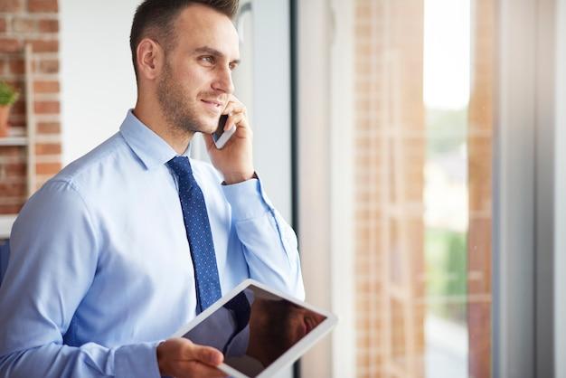 Uomo d'affari con tablet digitale e telefono cellulare