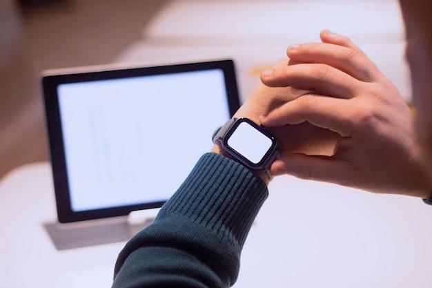 Uomo d'affari con tavoletta digitale con schermo bianco sul tavolo e smart watch sulla sua mano.