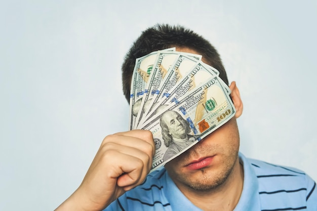 Uomo d'affari con una banconota in dollari attaccata agli occhi